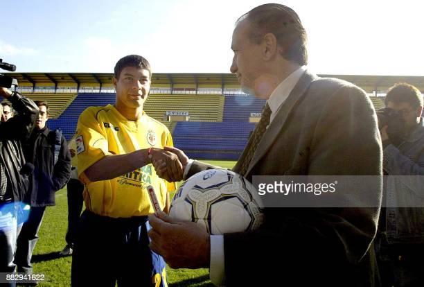 Villarreal's new Argentine international midfielder Sebastian Alejandro Battaglia shakes hand with Villarreal's president Fernando Roig during his...
