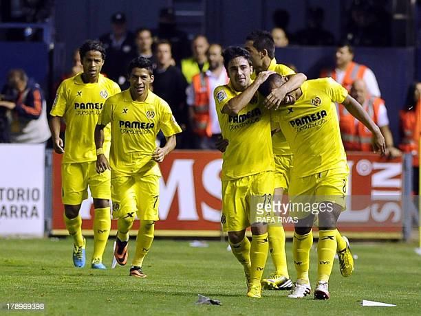 Villarreal's Nigerian forward Ikechukwu Uche celebrates his goal with teammates during the Spanish league football match Club Atletico Osasuna vs...
