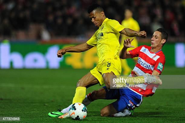 Villarreal's Nigerian forward Ikechukwu Uche vies with Granada's French midfielder Alexandre Coeff during the Spanish league football match Granada...