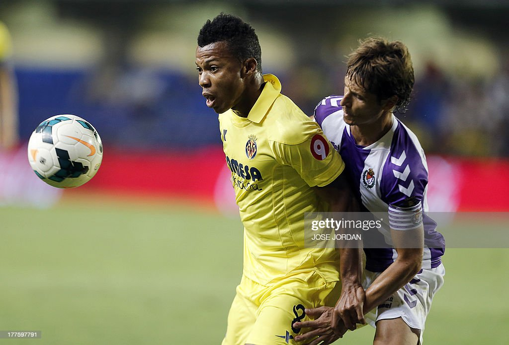 Villarreal's Nigerian forward Ikechukwu Uche (L) vies with Valladolid's midfielder Alvaro Rubio during the Spanish league football match Villarreal CF vs Real Valladolid FC de Madrid at El Madrigal stadium in Villareal on August 24, 2013.