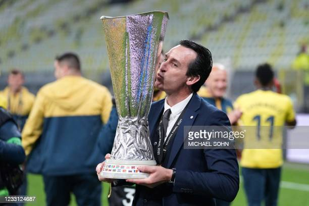Villarreal's Spanish coach Unai Emery poses for pictures with the trophy after winning the UEFA Europa League final football match between Villarreal...