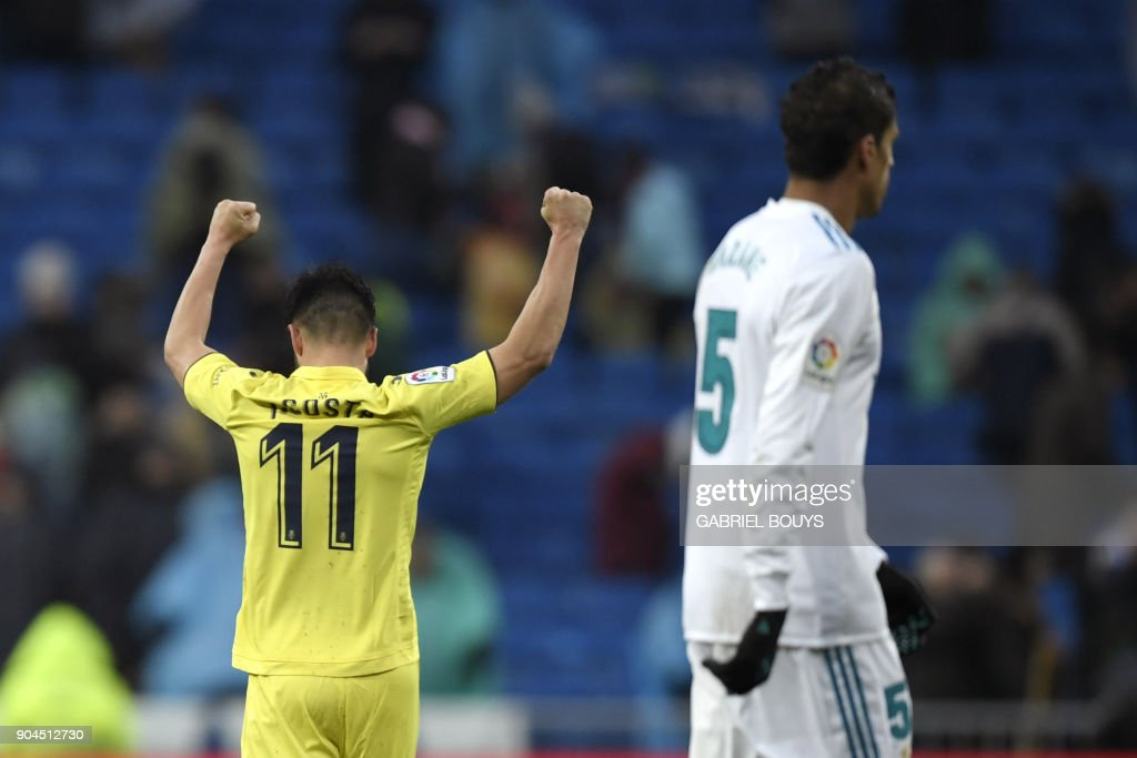 Villarreal's Spanish defender Jaume Costa celebrates next to Real Madrid's French defender Raphael Varane (R) at the end of the Spanish league football match between Real Madrid and Villarreal at the Santiago Bernabeu Stadium in Madrid on January 13, 2018. /