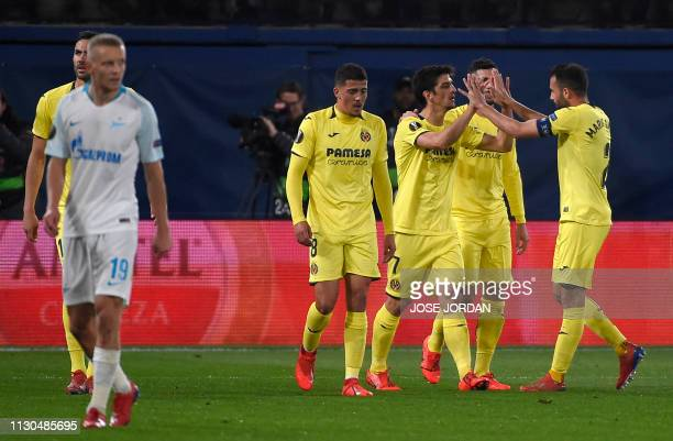 Villarreal's Spanish forward Gerard Moreno is congratulated by teammates after scoring a goal during the UEFA Europa League round of 16 second leg...
