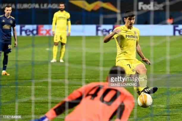 Villarreal's Spanish forward Gerard Moreno kicks and scores on a penalty during the UEFA Europa League quarter-final football match between Dinamo...