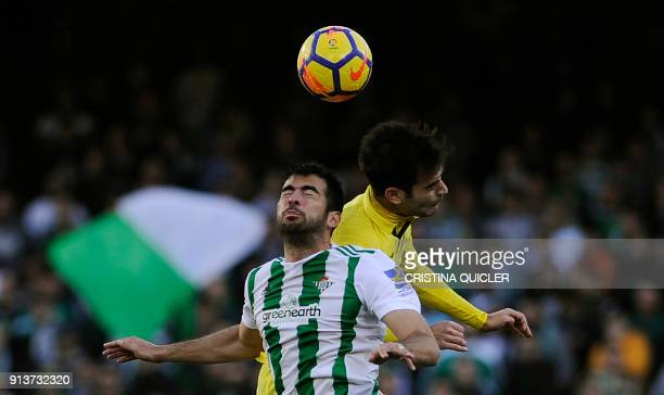 Villarreal's Spanish midfielder Manuel Trigueros Munoz jumps for the ball with Real Betis' Spanish defender Jordi Amat during the Spanish league...