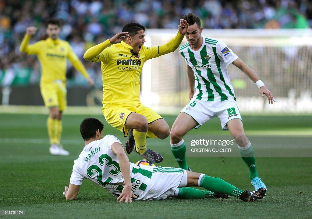Villarreal's Spanish midfielder Pablo Fornals (C) jumps over Real Betis' Algerian defender Aissa Mandi (down) during the Spanish league football match between Real Betis and Villarreal CF at the Benito Villamarin stadium in Sevilla on February 03, 2018. /