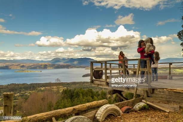 ビジャリカ湖:観光客は、照らされたピーク、山の湖の石、反射、真昼の青空と高い山との山の美しいパタゴニアの風景を楽しんでいます。 - リオネグロ州 ストックフォトと画像