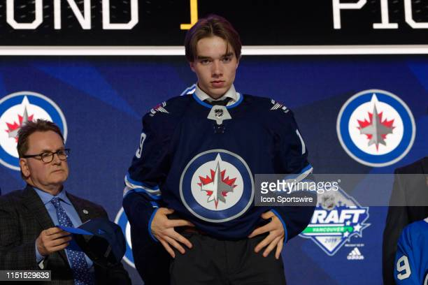 Ville Heinola puts on a jersey after being selected twentieth overall by the Winnipeg Jets during the first round of the 2019 NHL Draft at Rogers...