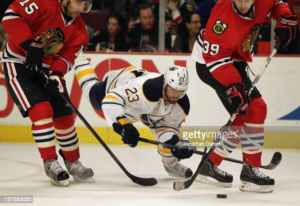 Ville Leino of the Buffalo Sabres falls to the ice trying for the puck between Andrew Brunette and Jimmy Hayes of the Chicago Blackhawks at the...