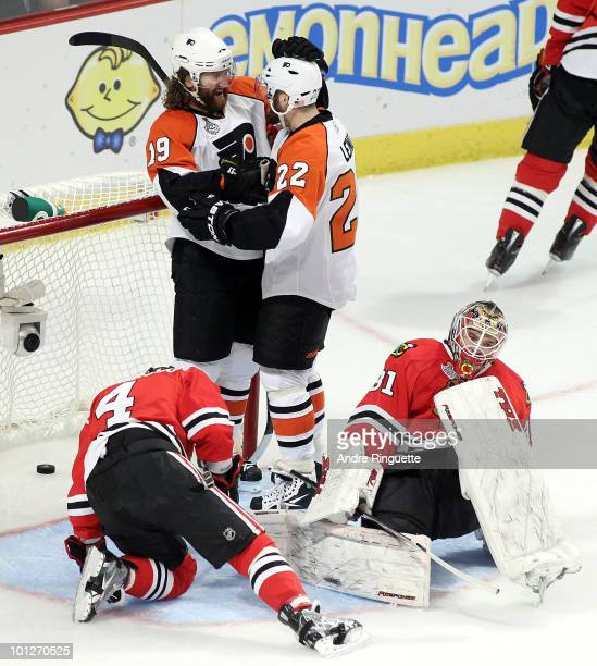 Ville Leino of the Philadelphia Flyers celebrates with teammate Scott Hartnell as goaltender Antti Niemi and Niklas Hjalmarsson of the Chicago...