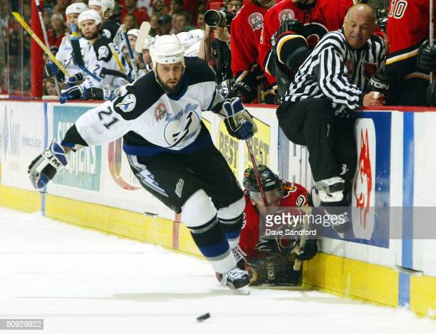 Ville Nieminen of the Calgary Flames is pushed into the boards by Cory Sarich of the Tampa Bay Lightning as linesman Ray Scapinello clears the way...