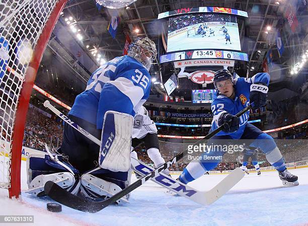 Ville Pokka of Team Finland pushes the puck away from the goalline in front of Pekka Rinne during the game against Team North America during the...