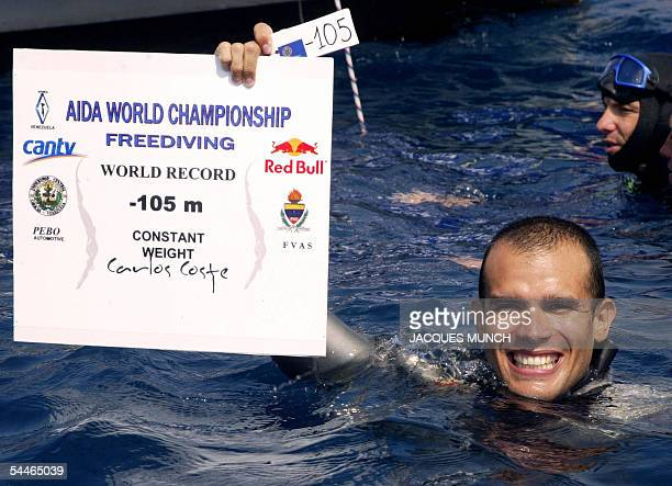 Villefranche-sur-Mer, FRANCE: Carlos Coste from Venezuela presents his minus 105 meters record tag after he wins the men individual free-diving world...