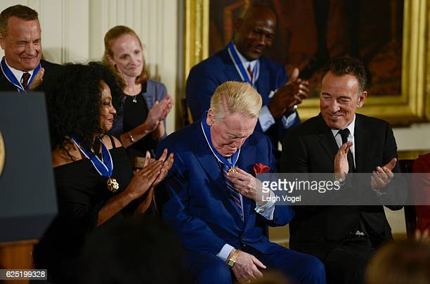 Vin Scully looks at his medal after being presented with the 2016 Presidential Medal Of Freedom by President Obama at the White House on November 22...
