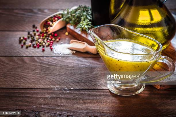 vinaigrette dressing with copy space on a rustic wooden table - salad dressing stock pictures, royalty-free photos & images