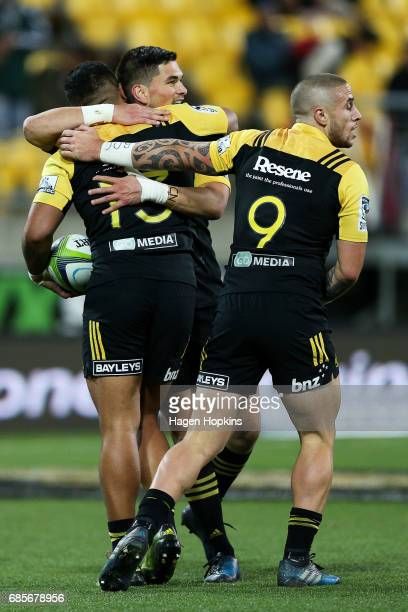 Vince Aso of the Hurricanes celebrates his try with teammates Otere Black and TJ Perenara during the round 13 Super Rugby match between the...