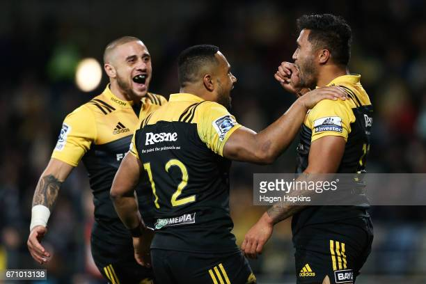 Vince Aso of the Hurricanes celebrates his try with teammates TJ Perenara and Ngani Laumape during the round nine Super Rugby match between the...