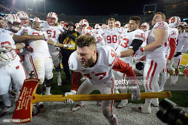 Vince Biegel of the Wisconsin Badgers uses Paul Bunyan's Axe to chop down the goal post after a win of the game against the Minnesota Golden Gophers...
