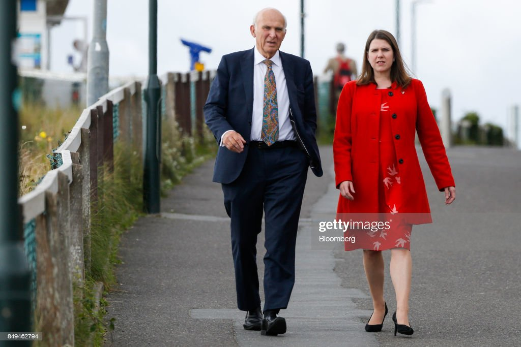Vince Cable, leader of the U.K.'s Liberal Democrat Party, left, arrives with Jo Swinson, deputy leader of the Liberal Democrat Party, ahead of his keynote speech at the party's annual conference in Bournemouth, U.K., on Tuesday, Sept. 19, 2017. Cable said U.K. Prime Minister Theresa May should fire her foreign secretary, Boris Johnson, over an article he published on Saturday about Britains departure from the European Union. Photographer: Luke MacGregor/Bloomberg via Getty Images