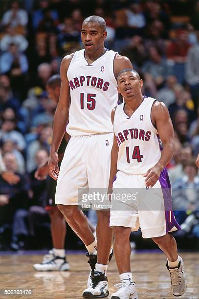 Vince Carter and Muggsy Bogues of the Toronto Raptors looks on against the Philadelphia 76ers on November 14 1999 at the Air Canada Centre in Toronto...