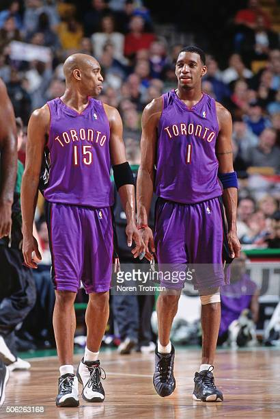 Vince Carter and Tracy McGrady of the Toronto Raptors chats against the Boston Celtics on March 1 2000 at the Fleet Center in Boston Massachusetts...