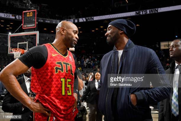 Vince Carter of the Atlanta Hawks talks with Former NBA Player Kobe Bryant after the game against the Brooklyn Nets on December 21 2019 at Barclays...