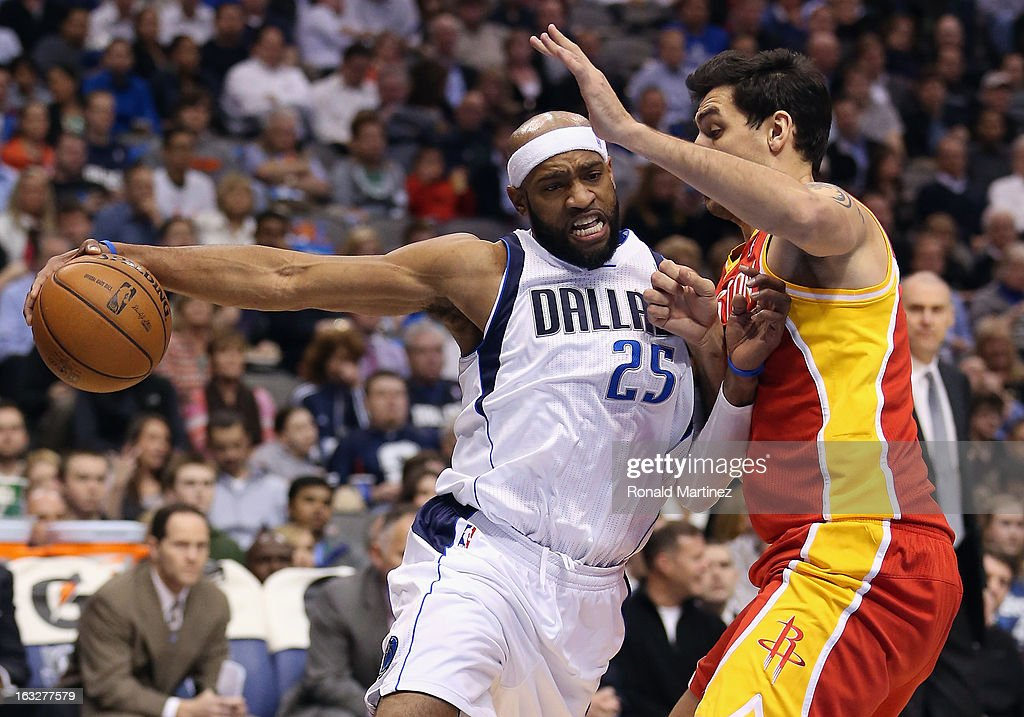 Vince Carter #25 of the Dallas Mavericks dribbles the ball against Carlos Delfino #10 of the Houston Rockets at American Airlines Center on March 6, 2013 in Dallas, Texas.