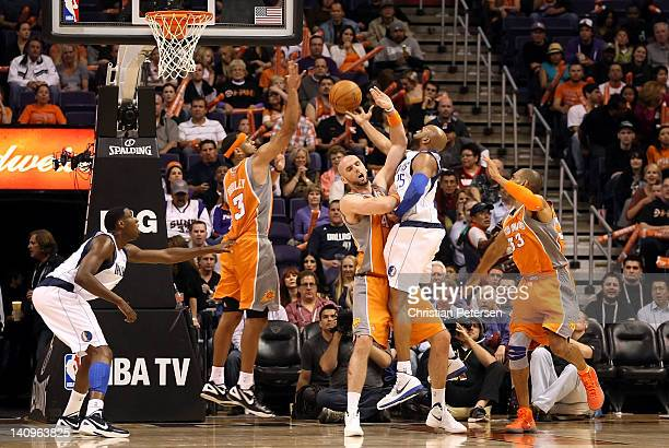 Vince Carter of the Dallas Mavericks is called for a charge against Marcin Gortat of the Phoenix Suns during the NBA game at US Airways Center on...