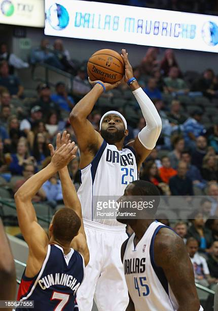 Vince Carter of the Dallas Mavericks takes a shot against Jared Cunningham of the Atlanta Hawks at American Airlines Center on October 23 2013 in...