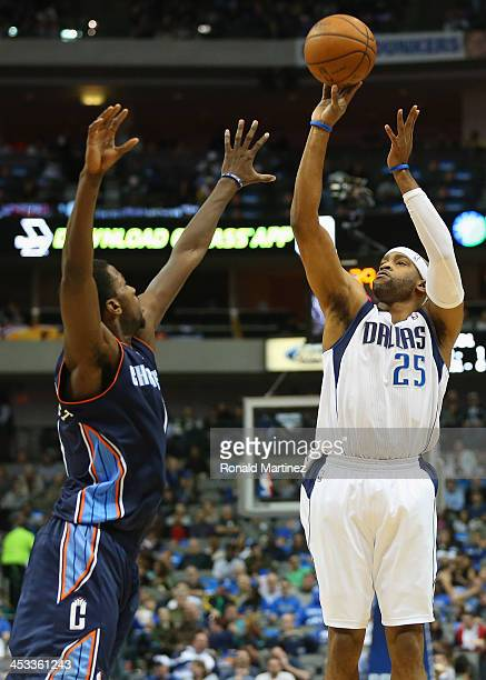 Vince Carter of the Dallas Mavericks takes a shot against Michael KiddGilchrist of the Charlotte Bobcats at American Airlines Center on December 3...