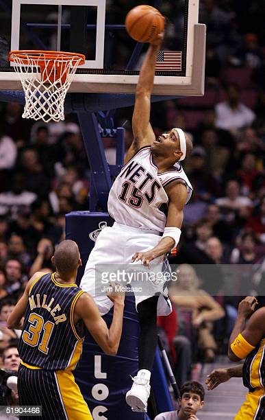 Vince Carter of the New Jersey Nets dunks a basket over Reggie Miller of the Indiana Pacers during their game on December 30, 2004 at Continental...