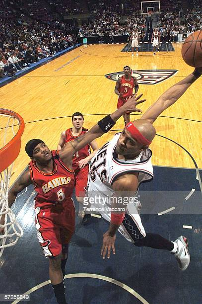 Vince Carter of the New Jersey Nets dunks against Josh Smith of the Atlanta Hawks on April 4 2006 at the Continental Airlines Arena in East...
