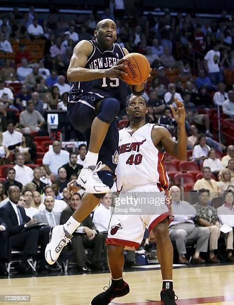 Vince Carter of the New Jersey Nets gets to the basket past Udonis Haslem of the Miami Heat at American Airlines Arena November 3, 2006 in Miami,...