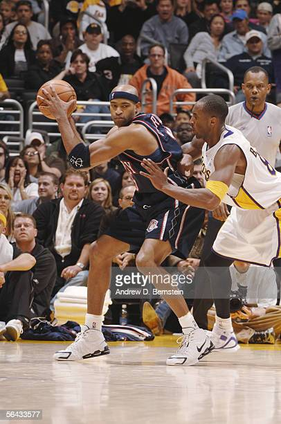 Vince Carter of the New Jersey Nets is defended by Kobe Bryant of the Los Angeles Lakers during the game at Staples Center on November 27 2005 in Los...