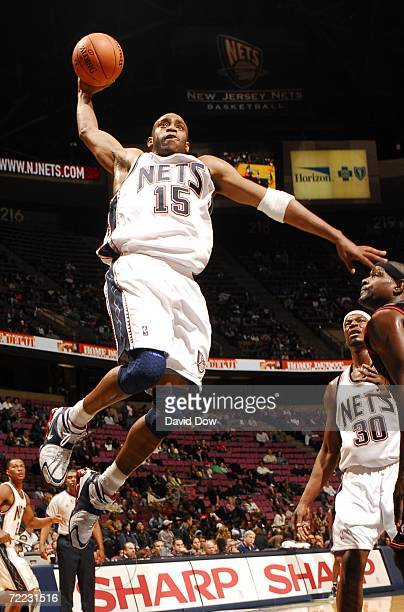 Vince Carter of the New Jersey Nets shoots against Chris Webber of the Philadelphia 76ers at the Continental Airlines Arena October 20 2006 in East...