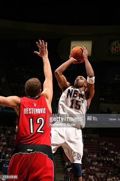 Vince Carter of the New Jersey Nets shoots against Rasho Nesterovic of the Toronto Raptors on November 1 2006 at Continental Airlines Arena in East...