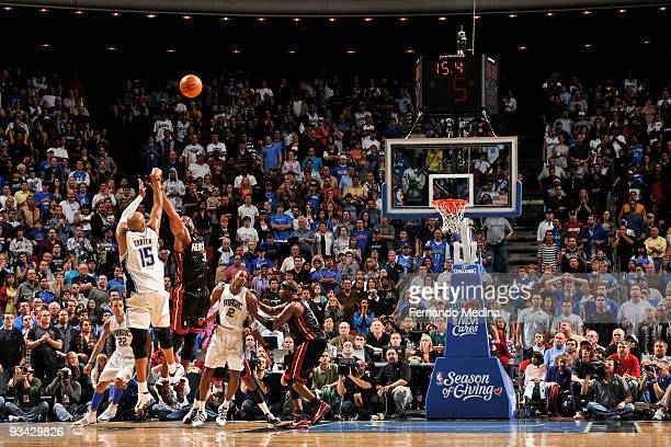 Vince Carter of the Orlando Magic attempts a three point shot against Dwyane Wade of the Miami Heat during the game on November 25 2009 at Amway...