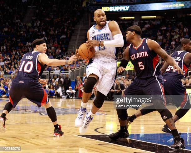 Vince Carter of the Orlando Magic drives between Mike Bibby and Josh Smith of the Atlanta Hawks during the game at Amway Arena on December 6 2010 in...