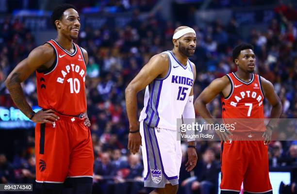 Vince Carter of the Sacramento Kings DeMar DeRozan and Kyle Lowry of the Toronto Raptors watch a free throw during the first half of an NBA game at...