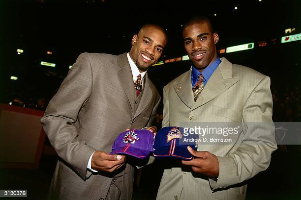Vince Carter of the Toronto Raptors and Antawn Jamison of the Golden State Warriors pose with their new team's hats on June 24, 1998 during the 1998...