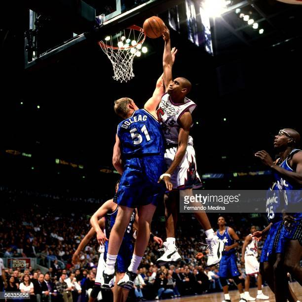 Vince Carter of the Toronto Raptors drives to the basket for a slam dunk against the Orlando Magic during an NBA game on April 19 1999 at Air Canada...