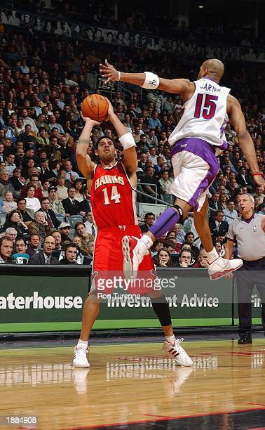 Vince Carter of the Toronto Raptors flies past Ira Newbie of the Atlanta Hawks during the NBA game at Air Canada Centre on March 19 2003 in Toronto...
