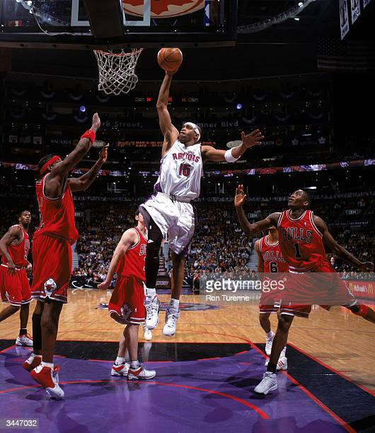 Vince Carter of the Toronto Raptors goes up for a dunk against Eddy Curry of the Chicago Bulls during a game at Air Canada Centre on April 11 2004 in...