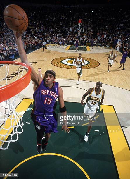 Vince Carter of the Toronto Raptors makes a dunk against the Seattle Sonics at Key Arena on November 12 2004 in Seattle Washington The Sonics won...