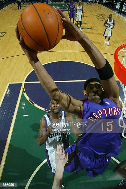 Vince Carter of the Toronto Raptors makes a dunk with Joe Smith of the Milwaukee Bucks close behind during the game on April 14 2004 at the Bradley...