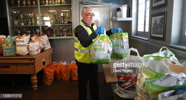 Vince Doherty a volunteer helper carries a food bag at the food bank set up by public house owner Teresa McCarthyDixon at the Swan and Helmet public...