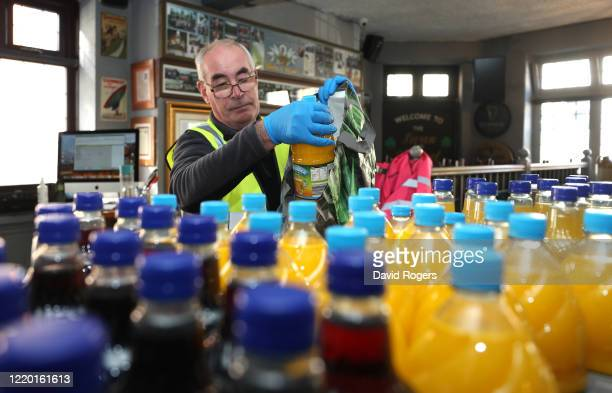 Vince Doherty a volunteer helper packs a food bag at the Swan and Helmet public house which was set up by public house owner Teresa McCarthyDixon for...