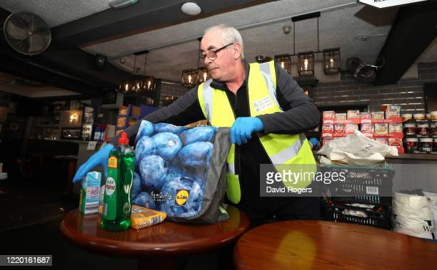 Vince Doherty a volunteer helper packs a food bag at the Swan and Helmet public house which was set up as a Food Bank by public house owner Teresa...