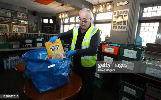 Vince Doherty a volunteer helper packs a food bag at the Swan and Helmet public house which has set up a Food Bank by public house owner Teresa...