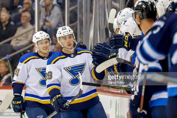 Vince Dunn and Vladimir Tarasenko of the St Louis Blues celebrate a second period goal against the Winnipeg Jets with teammates at the bench at the...